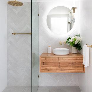 Idéer för ett mellanstort modernt beige badrum med dusch, med släta luckor, skåp i mellenmörkt trä, en hörndusch, grå kakel, porslinskakel, klinkergolv i porslin, ett fristående handfat, träbänkskiva, grått golv och med dusch som är öppen