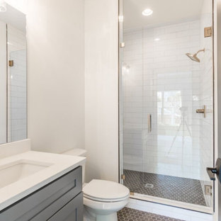 Inspiration for a mid-sized transitional kids' white tile and subway tile mosaic tile floor, gray floor, single-sink and brick wall double shower remodel in Atlanta with shaker cabinets, gray cabinets, a one-piece toilet, white walls, a drop-in sink, quartz countertops, a hinged shower door, white countertops and a built-in vanity