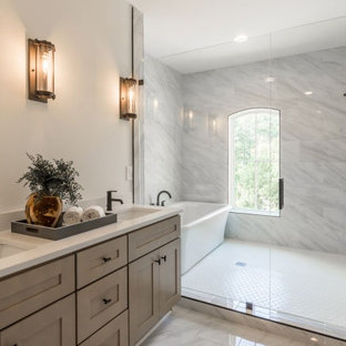 Large transitional master bathroom in Atlanta with shaker cabinets, brown cabinets, a freestanding tub, a double shower, a one-piece toilet, white tile, marble, white walls, mosaic tile floors, a drop-in sink, engineered quartz benchtops, white floor, a hinged shower door, white benchtops, a double vanity, a built-in vanity and brick walls.
