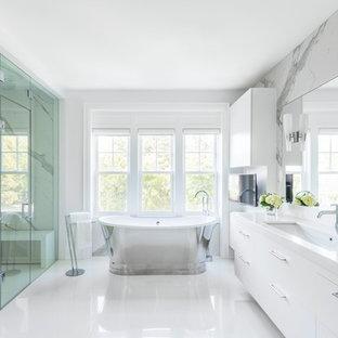 Réalisation d'une grand salle de bain principale design avec un placard à porte plane, des portes de placard blanches, une baignoire indépendante, un espace douche bain, un mur blanc, un sol blanc, une cabine de douche à porte battante, un carrelage gris, un carrelage blanc, du carrelage en marbre, un lavabo encastré et un plan de toilette en surface solide.