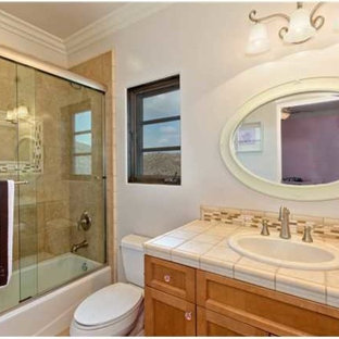 Design ideas for a large mediterranean family bathroom in San Diego with a built-in sink, raised-panel cabinets, dark wood cabinets, engineered stone worktops, a built-in bath, a shower/bath combination, a two-piece toilet, beige tiles, ceramic tiles, white walls and ceramic flooring.