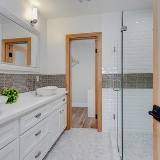 Mid-sized cottage 3/4 brown tile, white tile and subway tile mosaic tile floor and gray floor walk-in shower photo in Los Angeles with a vessel sink, shaker cabinets, white cabinets, white walls, granite countertops, a hinged shower door and white countertops