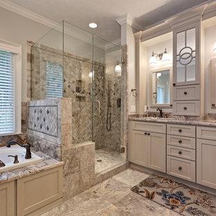 Идея дизайна: большая главная ванная комната в классическом стиле с накладной ванной, фасадами с утопленной филенкой, бежевыми фасадами, двойным душем, разноцветной плиткой, плиткой из травертина, полом из керамогранита, врезной раковиной, столешницей из гранита, душем с распашными дверями, раздельным унитазом, бежевыми стенами, бежевым полом, бежевой столешницей, нишей, тумбой под две раковины и встроенной тумбой