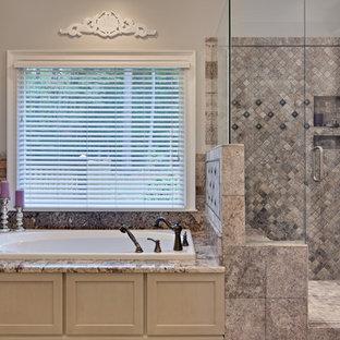 На фото: большая главная ванная комната в классическом стиле с бежевыми фасадами, накладной ванной, двойным душем, разноцветной плиткой, плиткой из травертина, столешницей из гранита, душем с распашными дверями, полом из керамогранита, фасадами с утопленной филенкой, раздельным унитазом, бежевыми стенами, врезной раковиной, бежевым полом, бежевой столешницей, сиденьем для душа, тумбой под две раковины и встроенной тумбой с