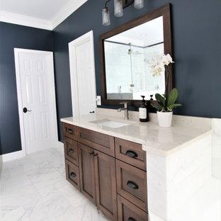 Großes Modernes Badezimmer En Suite mit Schrankfronten im Shaker-Stil, braunen Schränken, Eckbadewanne, Eckdusche, weißen Fliesen, Marmorfliesen, blauer Wandfarbe, Marmorboden, Unterbauwaschbecken, Quarzwerkstein-Waschtisch, weißem Boden, Falttür-Duschabtrennung und weißer Waschtischplatte in Atlanta