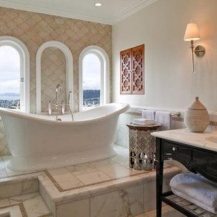 Esempio di una stanza da bagno padronale mediterranea con consolle stile comò, ante nere, vasca freestanding, pareti beige, lavabo sottopiano, piastrelle beige, piastrelle di vetro e top in marmo