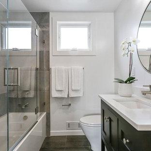 Imagen de cuarto de baño con ducha, minimalista, pequeño, con armarios estilo shaker, puertas de armario negras, encimera de cuarzo compacto, encimeras blancas, suelo de pizarra, bañera empotrada, combinación de ducha y bañera, sanitario de una pieza, baldosas y/o azulejos grises, baldosas y/o azulejos de pizarra, paredes grises, lavabo bajoencimera, suelo negro y ducha con puerta con bisagras