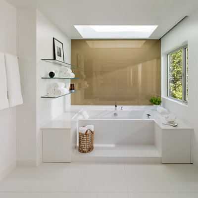 Example of a large trendy master white tile and porcelain tile porcelain tile bathroom design in San Francisco with white walls, flat-panel cabinets, white cabinets, a wall-mount toilet, an undermount sink and solid surface countertops