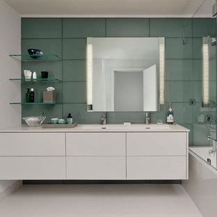 Ispirazione per una stanza da bagno padronale moderna di medie dimensioni con ante lisce, ante bianche, vasca ad alcova, vasca/doccia, piastrelle grigie, piastrelle verdi, piastrelle di vetro, lavabo rettangolare, pareti verdi, pavimento in gres porcellanato e top in superficie solida