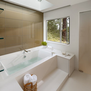 This is an example of a large contemporary master bathroom in San Francisco with white walls, flat-panel cabinets, white cabinets, an alcove tub, an alcove shower, a wall-mount toilet, white tile, porcelain tile, porcelain floors, an undermount sink and solid surface benchtops.