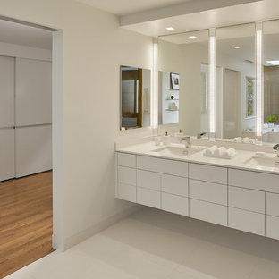 Modelo de cuarto de baño principal, actual, grande, con lavabo bajoencimera, armarios con paneles lisos, puertas de armario blancas, paredes blancas, baldosas y/o azulejos blancos, ducha empotrada, baldosas y/o azulejos de porcelana, encimera de acrílico, bañera empotrada, sanitario de pared y suelo de baldosas de porcelana
