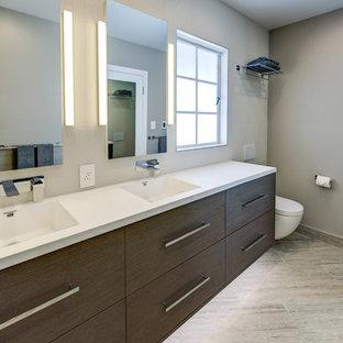 Foto de cuarto de baño principal, minimalista, de tamaño medio, con lavabo integrado, armarios con paneles lisos, puertas de armario de madera en tonos medios, encimera de acrílico, ducha empotrada, sanitario de pared, baldosas y/o azulejos grises, baldosas y/o azulejos de porcelana, paredes grises, suelo de baldosas de porcelana, suelo gris, ducha con puerta con bisagras y encimeras blancas