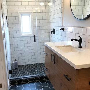 Cette photo montre une petit salle de bain principale rétro avec un placard à porte plane, des portes de placard en bois sombre, une douche ouverte, un WC suspendu, un carrelage blanc, des carreaux de céramique, un mur beige, un sol en carrelage de céramique, un lavabo encastré, un plan de toilette en quartz modifié, un sol noir et une cabine de douche à porte battante.
