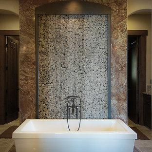 Foto de cuarto de baño principal, rural, extra grande, con bañera exenta, ducha doble, baldosas y/o azulejos marrones, suelo de baldosas tipo guijarro y paredes beige