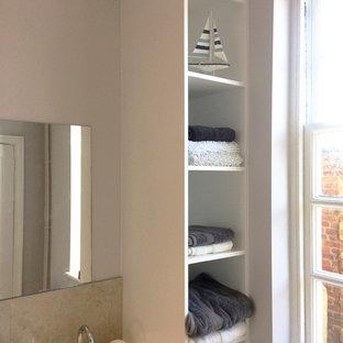 ケントの広いビーチスタイルのおしゃれなバスルーム (浴槽なし) (フラットパネル扉のキャビネット、白いキャビネット、オープン型シャワー、壁掛け式トイレ、ベージュのタイル、磁器タイル、グレーの壁、磁器タイルの床、壁付け型シンク、珪岩の洗面台) の写真