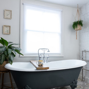 Design ideas for a small contemporary bathroom in London with a claw-foot bath, white walls and multi-coloured floors.