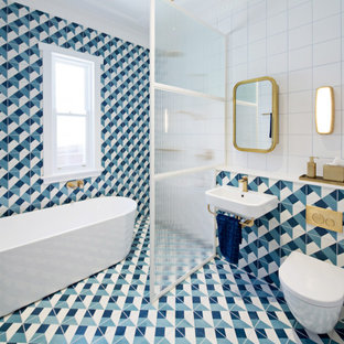 Inspiration for a contemporary bathroom in Sydney with a freestanding tub, a wall-mount toilet, blue tile, a vessel sink and multi-coloured floor.