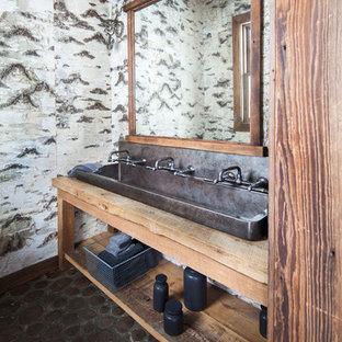Modelo de cuarto de baño con ducha, rústico, grande, con lavabo de seno grande, armarios abiertos, puertas de armario de madera oscura, suelo de baldosas tipo guijarro, encimera de madera, baldosas y/o azulejos de piedra, paredes multicolor y encimeras marrones