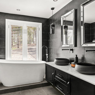 Design ideas for a large contemporary master bathroom in Sydney with black cabinets, a freestanding tub, gray tile, grey walls, ceramic floors, granite benchtops, white benchtops, a floating vanity, shaker cabinets, a vessel sink, grey floor and a double vanity.