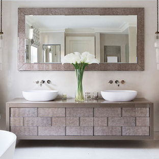 This is an example of a contemporary bathroom with beige cabinets, a freestanding bath, beige walls, a vessel sink, white floors and beige worktops.