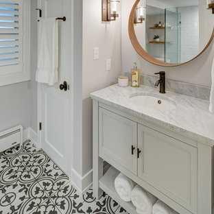 Example of a small cottage master white tile and subway tile cement tile floor and multicolored floor corner shower design in DC Metro with furniture-like cabinets, gray cabinets, a two-piece toilet, white walls, an undermount sink, marble countertops, a hinged shower door and white countertops