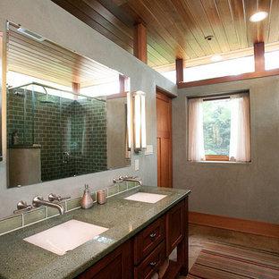Imagen de cuarto de baño con ducha, de estilo zen, de tamaño medio, con armarios con paneles empotrados, puertas de armario de madera oscura, ducha esquinera, baldosas y/o azulejos verdes, baldosas y/o azulejos de cemento, paredes grises, suelo de cemento, lavabo bajoencimera, encimera de vidrio reciclado y encimeras verdes