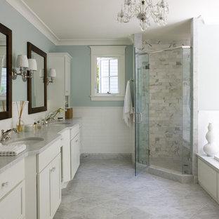 Bild på ett vintage badrum, med ett undermonterad handfat, luckor med infälld panel, vita skåp, en hörndusch, vit kakel, blå väggar och grått golv