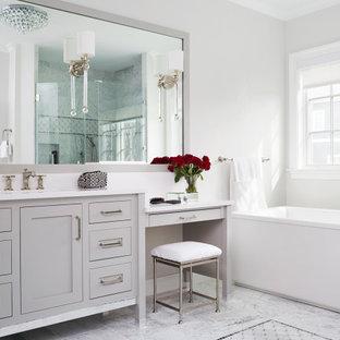 Klassisk inredning av ett stort vit vitt en-suite badrum, med luckor med infälld panel, grå skåp, ett fristående badkar, grå väggar, marmorgolv, ett undermonterad handfat, bänkskiva i kvarts och grått golv