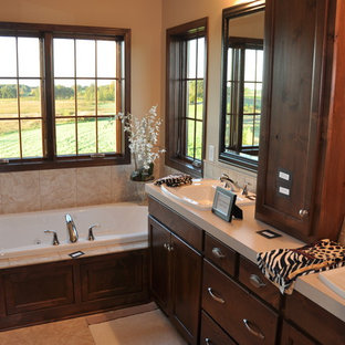 Inspiration for a timeless beige tile drop-in bathtub remodel in Minneapolis with a drop-in sink, raised-panel cabinets and dark wood cabinets