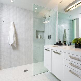 На фото: большая ванная комната в современном стиле с плоскими фасадами, белыми фасадами, душем в нише, белой плиткой, полом из терраццо, душевой кабиной, врезной раковиной, белым полом и белой столешницей