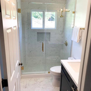 Inspiration for a small modern 3/4 white tile and subway tile marble floor and white floor alcove shower remodel in Los Angeles with shaker cabinets, black cabinets, a two-piece toilet, white walls, an undermount sink, solid surface countertops, a hinged shower door and white countertops