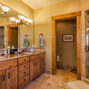 他の地域の大きいラスティックスタイルのおしゃれなマスターバスルーム (インセット扉のキャビネット、中間色木目調キャビネット、ドロップイン型浴槽、コーナー設置型シャワー、ベージュのタイル、石タイル、ベージュの壁、トラバーチンの床、アンダーカウンター洗面器、御影石の洗面台) の写真