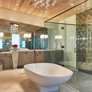 ロサンゼルスの大きいコンテンポラリースタイルのおしゃれなマスターバスルーム (フラットパネル扉のキャビネット、中間色木目調キャビネット、置き型浴槽、ダブルシャワー、グレーのタイル、メタルタイル、ベージュの壁、ライムストーンの床、アンダーカウンター洗面器、珪岩の洗面台) の写真