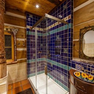 バンクーバーの中サイズのおしゃれなマスターバスルーム (家具調キャビネット、アルコーブ型浴槽、コーナー設置型シャワー、一体型トイレ、青いタイル、セラミックタイル、白い壁、セラミックタイルの床、オーバーカウンターシンク、木製洗面台、オレンジの床、開き戸のシャワー) の写真