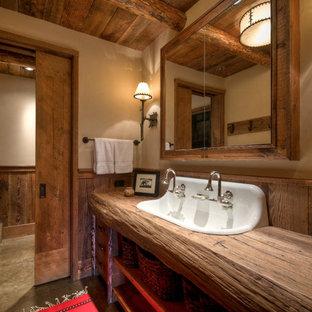 Modelo de cuarto de baño con ducha, rural, de tamaño medio, con encimera de madera, armarios con paneles lisos, sanitario de dos piezas, baldosas y/o azulejos marrones, paredes beige, suelo de cemento, lavabo encastrado, puertas de armario de madera oscura y encimeras marrones