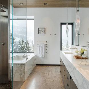 Ejemplo de cuarto de baño principal, rústico, con armarios con paneles lisos, puertas de armario de madera en tonos medios, bañera encastrada sin remate, ducha a ras de suelo, paredes blancas, lavabo bajoencimera, encimera de mármol, suelo gris y encimeras blancas