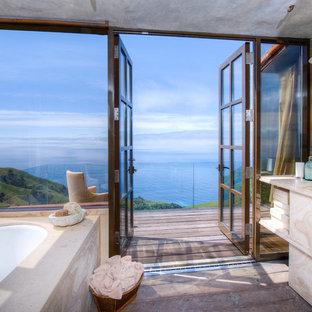 Foto di un'ampia stanza da bagno padronale mediterranea con vasca sottopiano e pavimento in legno massello medio
