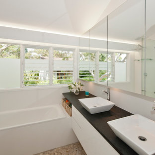 Example of a mid-sized trendy master beige tile pebble tile floor bathroom design in Sydney with a vessel sink, flat-panel cabinets, white cabinets, solid surface countertops and white walls