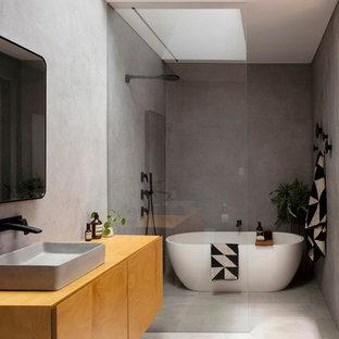 Идея дизайна: главная ванная комната в стиле модернизм с плоскими фасадами, фасадами цвета дерева среднего тона, отдельно стоящей ванной, душевой комнатой, серой плиткой, серыми стенами, настольной раковиной, столешницей из дерева, серым полом, открытым душем и коричневой столешницей