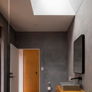 Design ideas for a modern 3/4 bathroom in Sydney with flat-panel cabinets, medium wood cabinets, a one-piece toilet, gray tile, grey walls, a vessel sink, wood benchtops, grey floor and brown benchtops.