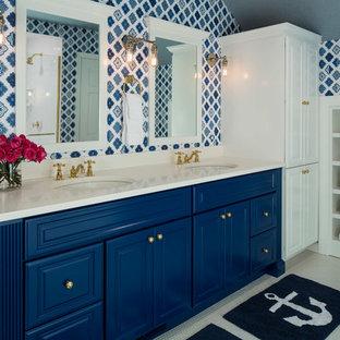 Imagen de cuarto de baño costero con lavabo bajoencimera, armarios con paneles con relieve, puertas de armario azules y paredes multicolor