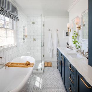 サンフランシスコの中くらいのビーチスタイルのおしゃれなマスターバスルーム (シェーカースタイル扉のキャビネット、青いキャビネット、置き型浴槽、コーナー設置型シャワー、白いタイル、セラミックタイル、白い壁、大理石の床、アンダーカウンター洗面器、クオーツストーンの洗面台、グレーの床、開き戸のシャワー、白い洗面カウンター、ニッチ、洗面台2つ) の写真