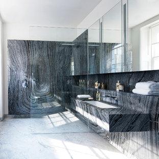 Diseño de cuarto de baño principal, minimalista, grande, con armarios tipo vitrina, puertas de armario grises, bañera encastrada, ducha a ras de suelo, sanitario de pared, baldosas y/o azulejos negros, losas de piedra, paredes negras, suelo de mármol, lavabo encastrado, encimera de mármol, suelo gris y ducha abierta