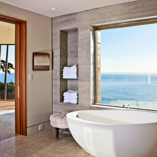 Example of a large coastal master cement tile limestone floor and beige floor freestanding bathtub design in Los Angeles with gray walls