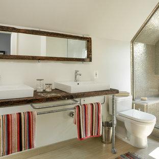 Industrial Badezimmer mit Aufsatzwaschbecken, Waschtisch aus Holz, Duschnische, Toilette mit Aufsatzspülkasten, beigefarbenen Fliesen und Mosaikfliesen in Detroit