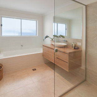 Design ideas for a beach style master bathroom in Sunshine Coast with beige tile, ceramic tile, ceramic floors, a vessel sink, beige floor, a hinged shower door, brown benchtops, a drop-in tub, flat-panel cabinets, medium wood cabinets, a corner shower, beige walls and wood benchtops.