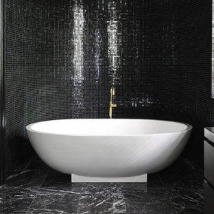 Idee per un'ampia stanza da bagno padronale design con ante lisce, ante nere, vasca freestanding, zona vasca/doccia separata, WC monopezzo, piastrelle nere, lastra di vetro, pareti nere, pavimento in marmo, lavabo sottopiano, top in marmo, pavimento nero e porta doccia scorrevole