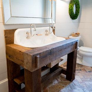 Lantlig inredning av ett mellanstort badrum, med öppna hyllor, grå väggar, tegelgolv, ett avlångt handfat och träbänkskiva