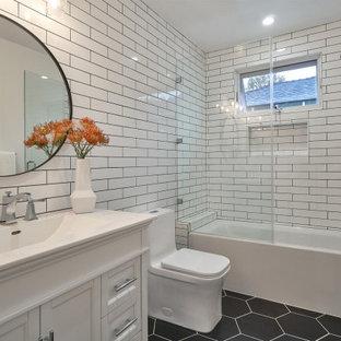 Foto di una stanza da bagno minimalista di medie dimensioni con ante in stile shaker, ante bianche, vasca sottopiano, vasca/doccia, WC monopezzo, piastrelle multicolore, piastrelle in ceramica, pavimento in gres porcellanato, top in superficie solida, pavimento nero, top bianco e un lavabo