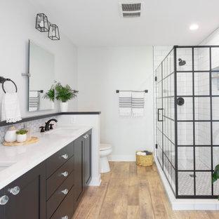 Inspiration för ett mellanstort funkis vit vitt en-suite badrum, med svarta skåp, en hörndusch, en toalettstol med separat cisternkåpa, vit kakel, tunnelbanekakel, vinylgolv, ett undermonterad handfat, bänkskiva i kvarts, brunt golv, dusch med gångjärnsdörr, grå väggar och skåp i shakerstil